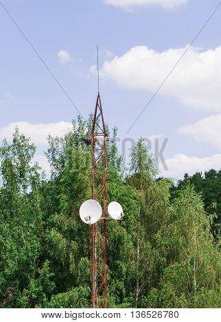 Round two satellite television antennas on metal tower