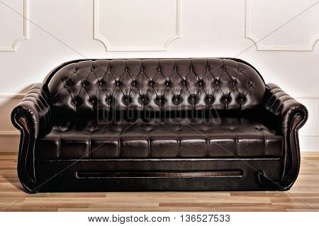 Brown leather sofa near white decorated wall