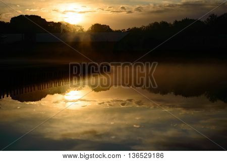 Beautiful sunset reflection over a tranquil freshwater lake with the fiery orb of the sun and scattered clouds mirrored on the surface of the calm water at dusk