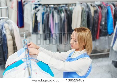 Girl worker hangs Laundry clean clothes on a hanger in the dry cleaner