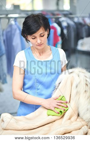 Girl Laundry worker is wiping the coat with a cloth