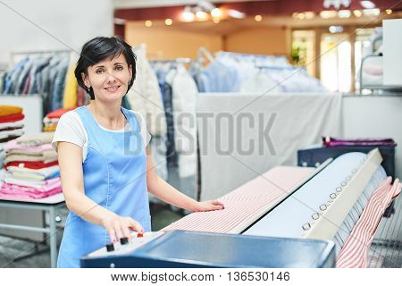 Woman Laundry worker pats the linen on the automatic machine at the dry cleaners