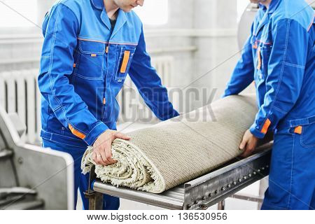 Men workers cleaning get carpet from an automatic washing machine and carry it in the clothes dryer in the Laundry room