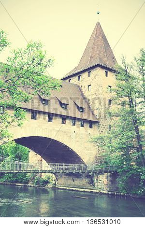 Old tower and bridge in Nuremberg, Germany. Retro style filtered image