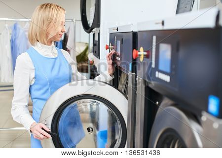 Girl Laundry worker selects a wash program at the dry cleaners
