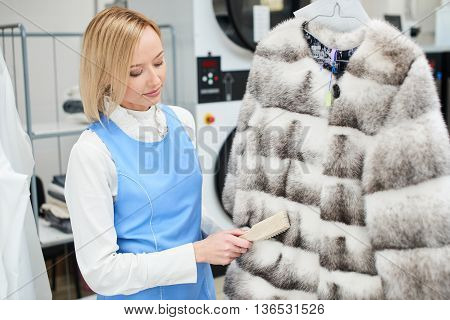 Girl worker performs dry Laundry, hand cleaning fur garments in dry cleaning