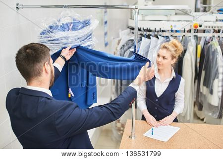 Male customer checks clean clothes, when it is received at the dry cleaners