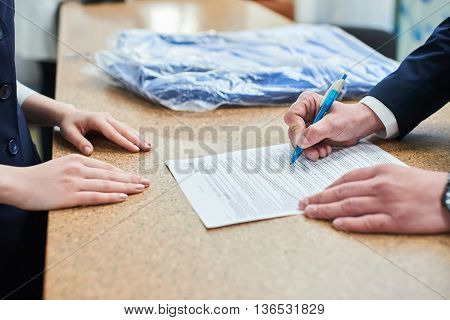 Male hand signing a document with a ballpoint pen