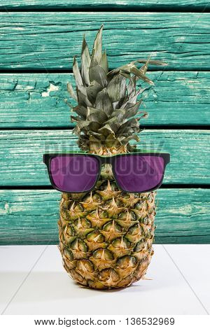 Summer Pineapple In Sunglasses On Wood Background