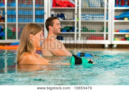 Couple exercising Aquarobics or hydrotherapy in spa