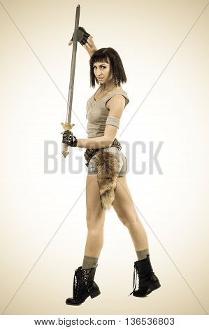 Styled portrait of young warrior woman holding sword on white background in full length.