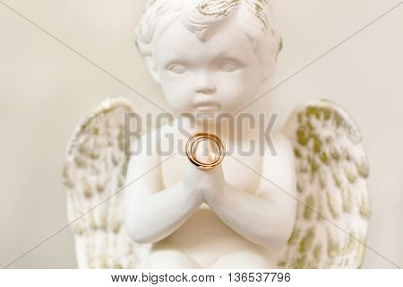 wedding rings in the hands of an angel