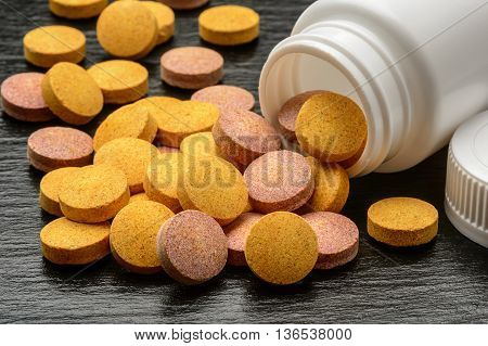 Vitamin and mineral pills on black background.