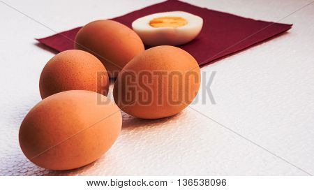 four orange boiled eggs lie on a light uneven surface, a half of the cut egg lies on a napkin of claret color,