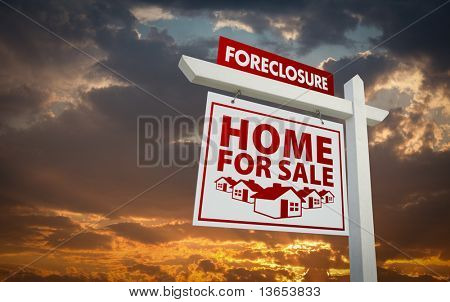 White and Red Foreclosure Home For Sale Real Estate Sign Over Beautiful Clouds and Sunset Sky.