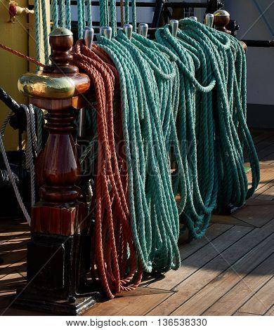 Rigging of a sailing ship, green and red ropes, blocks