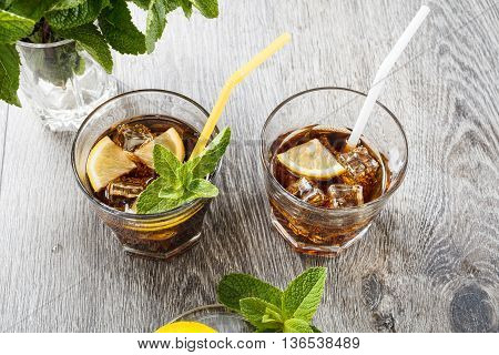 The cooling drink with ice, lemon and mint. Cola in glass on a wooden table.
