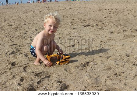 Little Boy Playing On The Beach In Summer