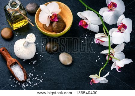 Spa setting with white orchid herbal massage ball and essential oil. Wellness concept