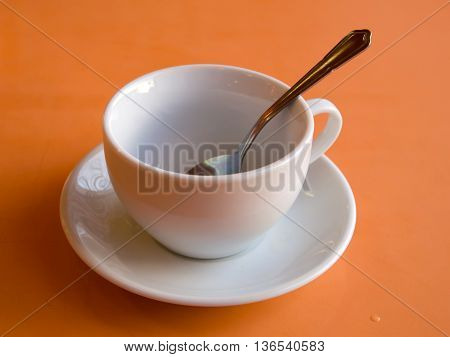 Metal spoon in a ceramic cup on an orange background