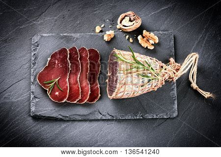 Gourmet dinner concept with sliced dry meat and walnuts. Copyspace
