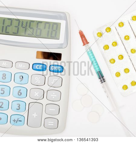 Calculator, Syringe And Pills On Grey Background