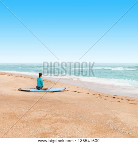 Outdoors shot of a lady surfer waiting at a seashore for a big waves to come