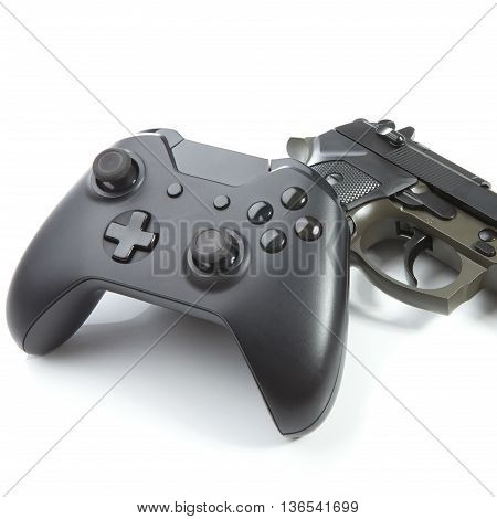 Close up studio shot of a game controller with real handgun near it - virtual and real life concept