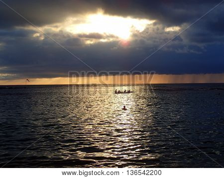 Sunset through the clouds and reflecting on the Pacific ocean with people playing and canoeing in the water of Oahu Hawaii. December 2015.
