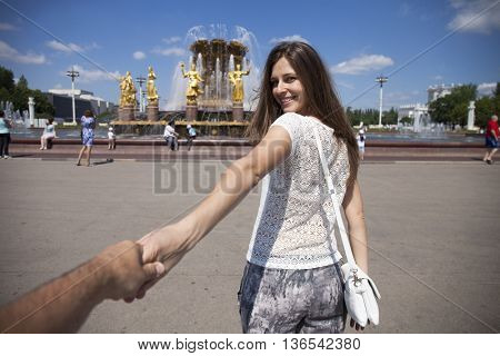 Follow me. Young happy woman holding the hand of her boyfriend