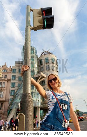 Beautiful happy young female traveler swirls around a traffic lighter in front of the Dancing House. Prague. Travel Czech Republic. Blonde girl having fun in the street near Dancing House. Europe.