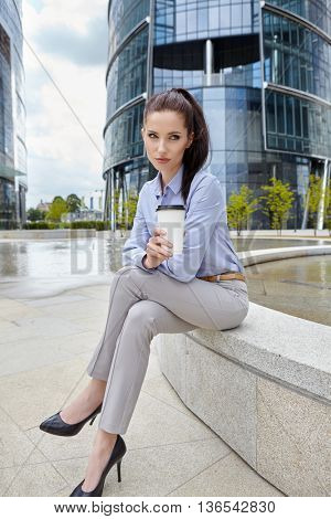 Beautiful young businesswoman with a disposable coffee cup, drinking coffee