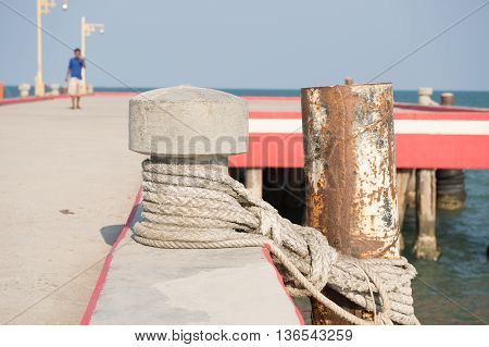 Close-up of mooring bollard with rope in marina