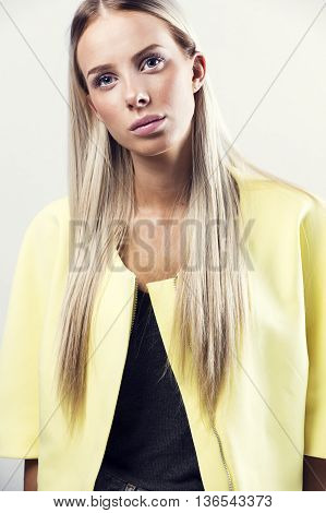 Fashion photo of a beautiful young woman with blonde hair in a yellow jacket. Natural retouched studio portrait.