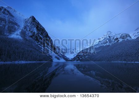 SNOW ON LAKE LOUISE AT NIGHT, VERY EARLY MORNING SUNRISE WITH THE MOUNTAINS REFLECTING IN THE LAKE