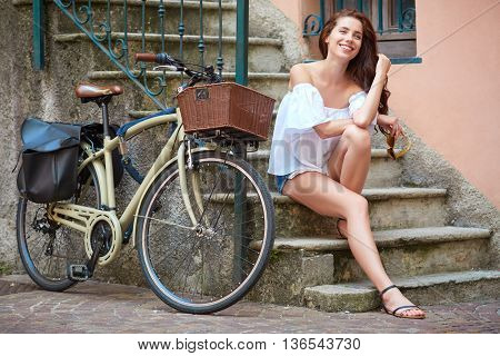 Young stylish woman with a bicycle in a city street.