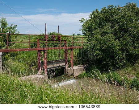 Open floodgate on the irrigation canal in agricultural land