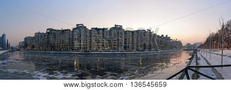 Bucharest, ROMANIA - January 22 2016: Dambovita river frozen in the center of Bucharest at sunset. View towards Unirii Boulevard and the Parliament building. BUCHAREST - January 22 2016
