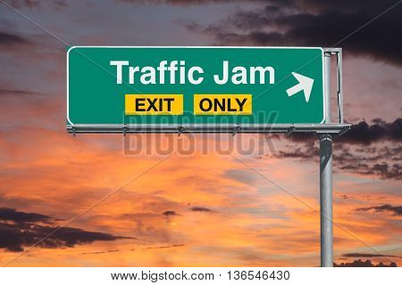 Traffic jam exit only freeway sign with sunrise sky.
