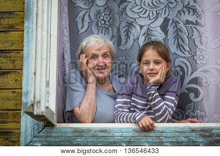 Grandmother with a small granddaughter together look out of the window of the house.