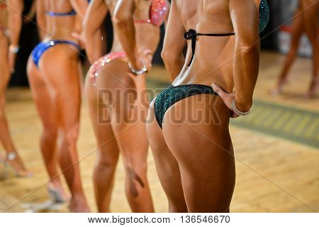 Fitness bikini competition, side view of female buttocks.