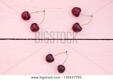 Fresh juicy cherry on pink wood background