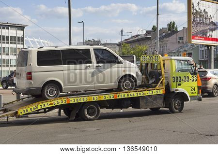 KIEV UKRAINE - JUNE 3 2016: A tow truck picking up a car being badly parked in Kiev Ukraine