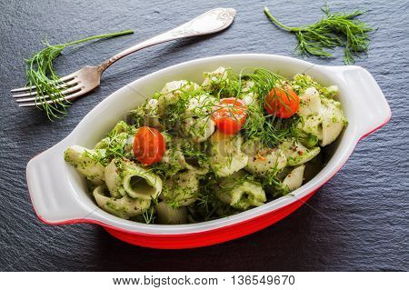 Broccoli pasta (shell shape) with dill and spices in baking dish on dark stone background.