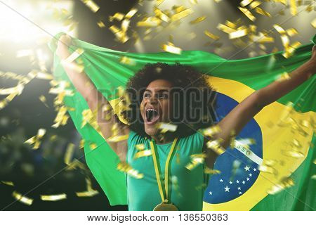 Female athlete holding the Brazilian flag in the stadium