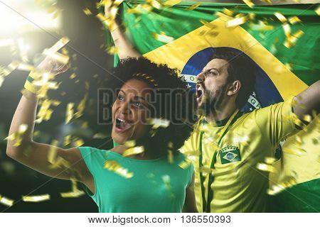 Brazilian athlete couple holding flag of Brazil