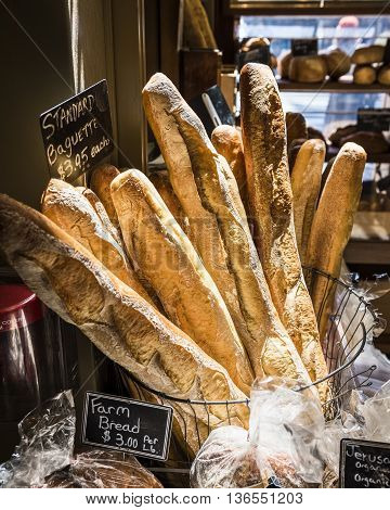 Baguettes in early morning sunlight by a windowsill in a bakery with other breads