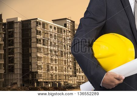 Engineer Holding Yellow Helmet For Workers Security On Contruction Background