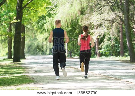 Rear View Of Young Athletic Couple Jogging In Park