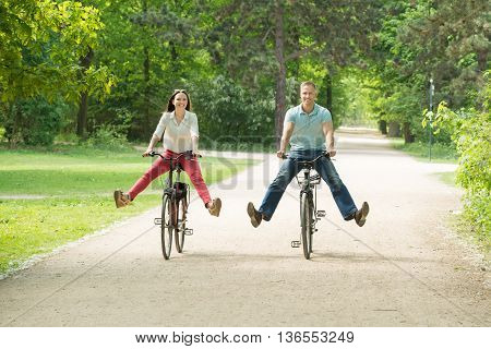 Young Happy Couple Riding Bicycle In Park At Morning